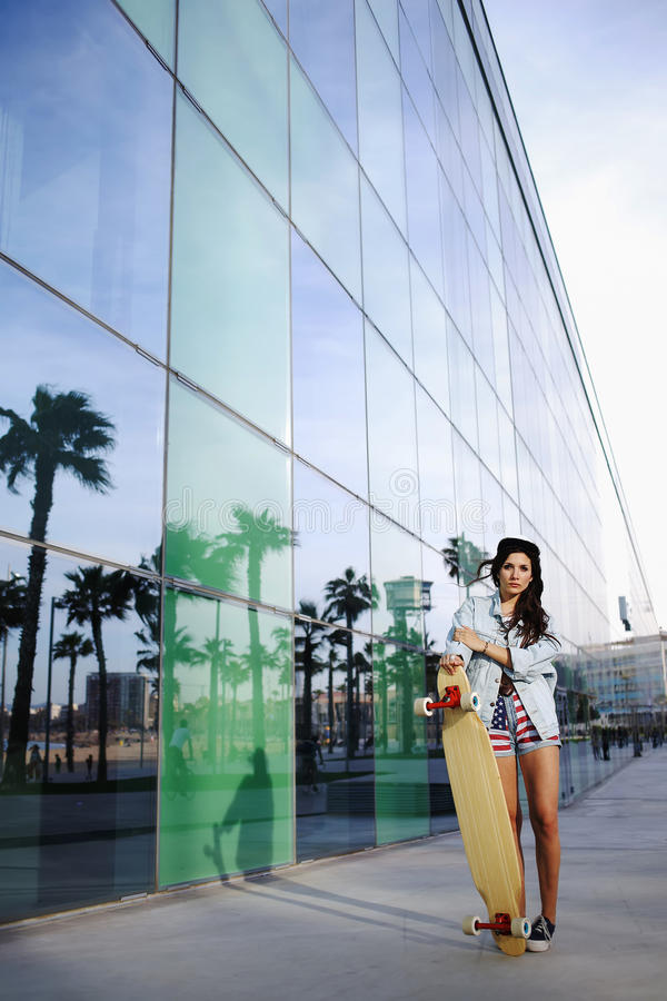 Het charmante jonge vrouw kijken aan het skateboard van de cameraholding stock afbeeldingen