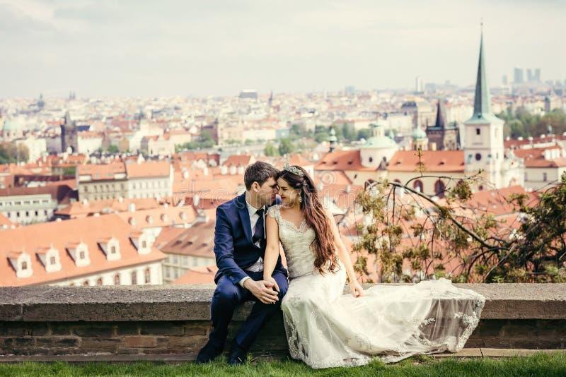 Het charmante jonggehuwdepaar houdt handen terwijl het zitten bij de achtergrond van het panorama van Praag royalty-vrije stock afbeelding