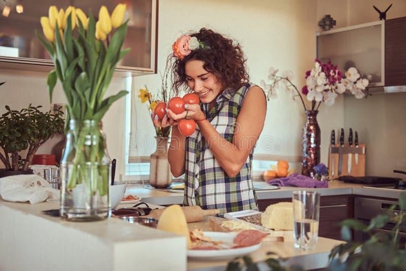 Het charmante krullende Spaanse meisje koken in haar keuken royalty-vrije stock foto's