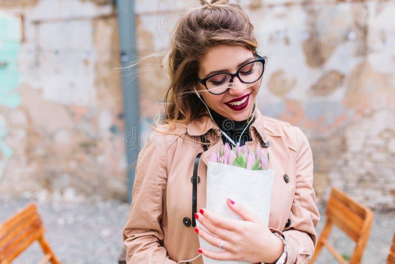 Het charmante meisje die glazen dragen ontving mooie bloemen als gift op de verjaardag Vrij jonge vrouw in beige laag stock foto