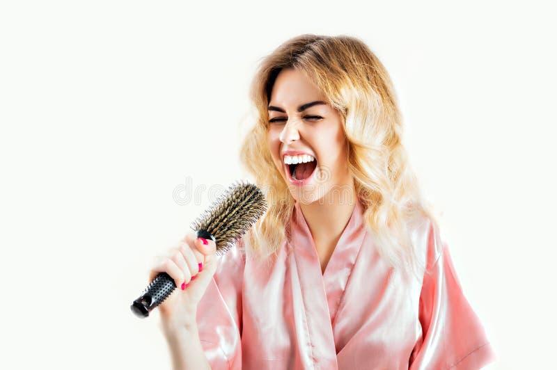 Het charmante meisje in een peignoir wordt gezongen in een kam royalty-vrije stock foto's