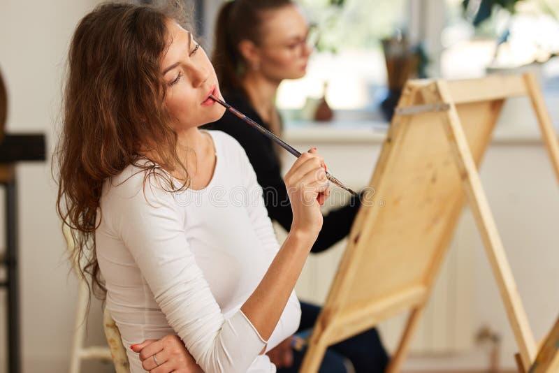 Het charmante meisje met bruin krullend haar gekleed in witte blouse creeert een beeld die bij de schildersezel de borstel in haa stock foto