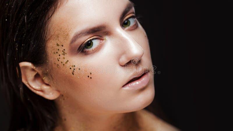 Het charmante meisje met in schittert make-up, schittert de modieuze samenstelling met goud op de jukbeenderen en nadert de ogen royalty-vrije stock foto