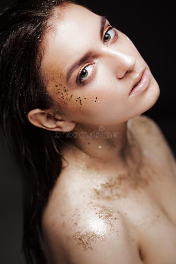 Het charmante meisje met in schittert make-up, schittert de modieuze samenstelling met goud op de jukbeenderen en nadert de ogen royalty-vrije stock afbeelding
