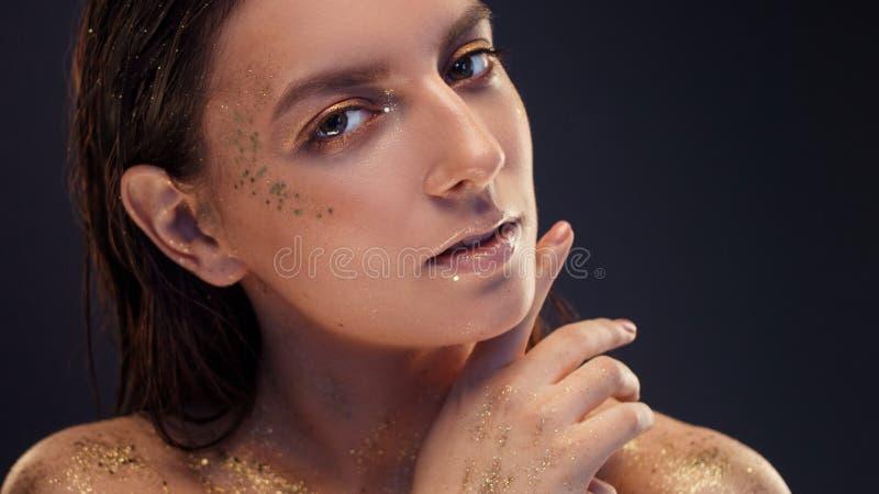 Het charmante meisje met in schittert make-up, schittert de modieuze samenstelling met goud op de jukbeenderen en nadert de ogen stock afbeeldingen