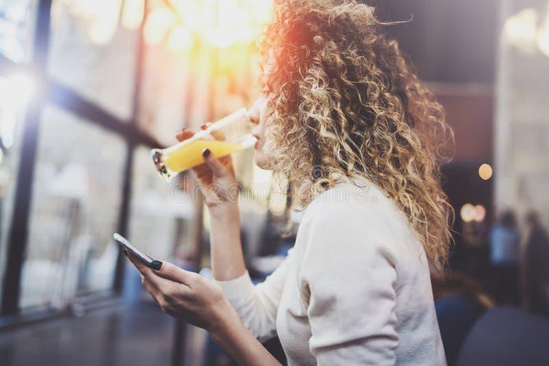 Het charmante mooie jonge bericht van de vrouwenlezing e-mail op mobiele telefoon tijdens rusttijd in koffiewinkel Bokeh en gloed royalty-vrije stock fotografie