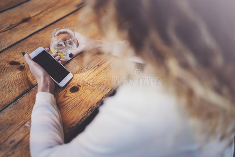 Het charmante mooie jonge bericht van de vrouwenlezing e-mail op mobiele telefoon tijdens rusttijd in koffiewinkel Bokeh en gloed stock foto's