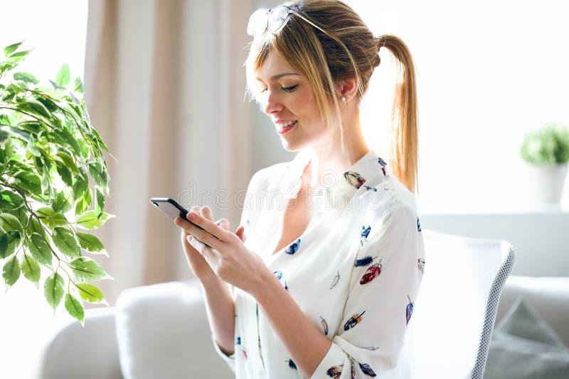 Het charmante mooie jonge ontwerpervrouw texting met haar mobiele telefoon op het kantoor stock fotografie