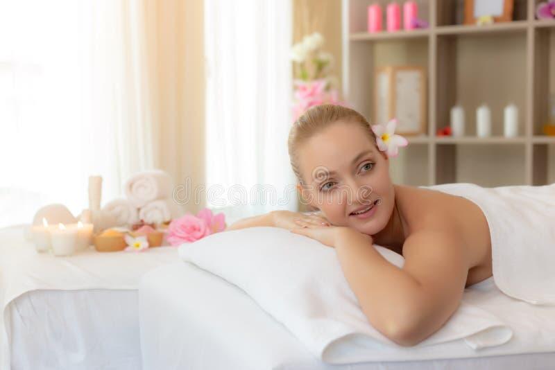 Het charmante mooie vrouw bepalen op bed bij kuuroordruimte Het aantrekkelijke mooie meisje kijkt rond de kuuroordsalon Schittere stock foto