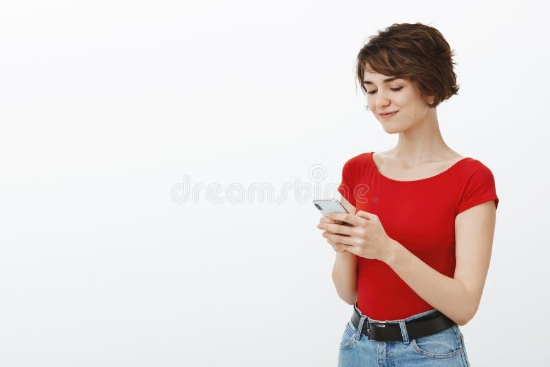 Het charmante verleidelijke jonge Europese smartphone van de het kapselgreep van het vrouwen korte elf verrukt glimlachen geïntri royalty-vrije stock foto's