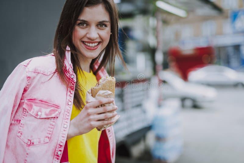 Het charmante vrouwelijke lopen openlucht met hotdog stock afbeelding