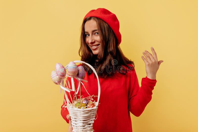 Het charmeren van aanbiddelijke Europese vrouw die rode trui dragen en het rode baret stellen over gele achtergrond met Pasen-man royalty-vrije stock afbeeldingen