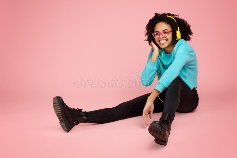 Het charmeren van Afrikaanse Amerikaanse jonge vrouw met heldere glimlach kleedde zich in vrijetijdskleding, glazen en hoofdtelef stock afbeeldingen