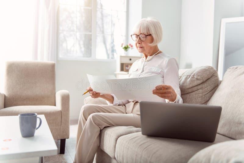 Het charmeren van bejaarde dame die grafieken op printouts vergelijken royalty-vrije stock foto's