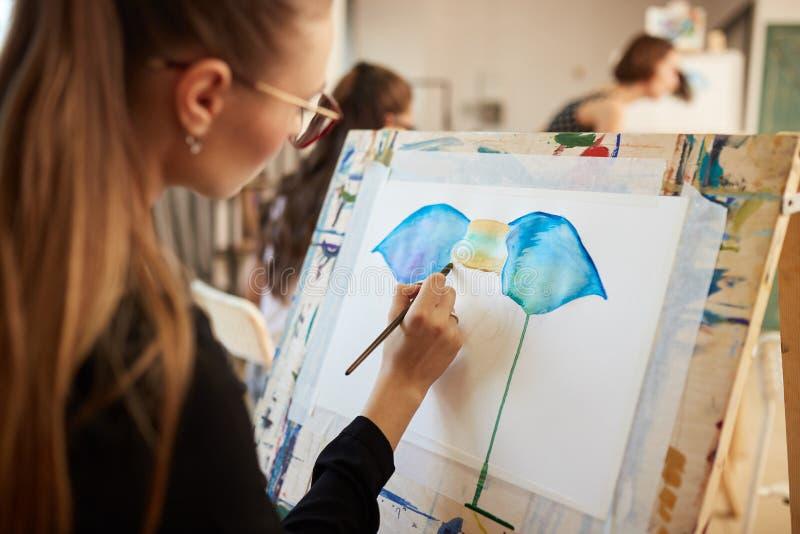 Het charmeren van blond meisje in glazen kleedde zich in zwarte blouse a zit bij de schildersezel en ts een beeld in de kunststud stock fotografie