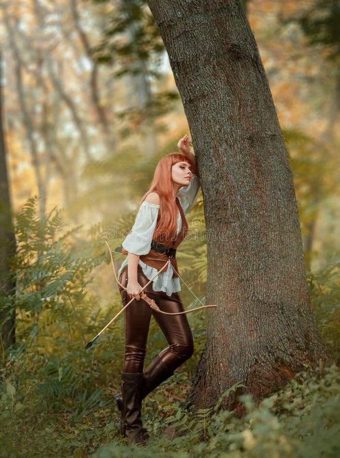 Het charmeren van bosrover rust het leunen van tegen een boom in het de herfst oranje bos een mooi meisje met helder rood haar royalty-vrije stock afbeelding