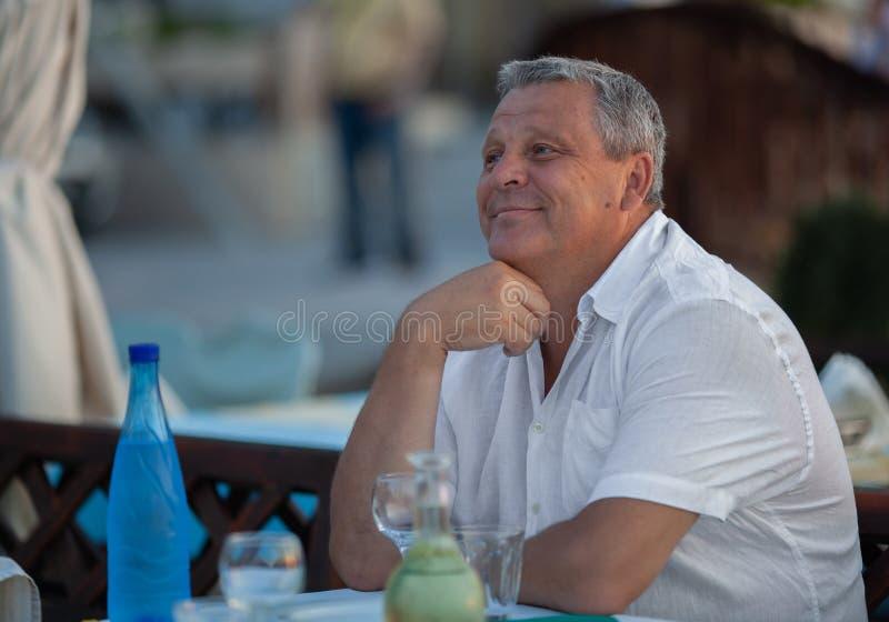 Het charmeren van de rijpe mens in openluchtkoffie royalty-vrije stock afbeelding