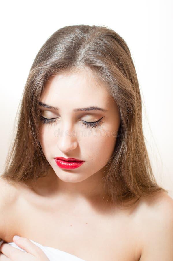 Het charmeren van donkerbruine jonge vrouw met rode lippen sloot ogen & naakte schouders op witte achtergrond royalty-vrije stock foto