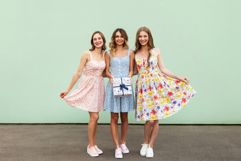Het charmeren van drie mooie jonge volwassen vrienden met kleding en huidige doos die en camera glimlachen bekijken royalty-vrije stock afbeelding