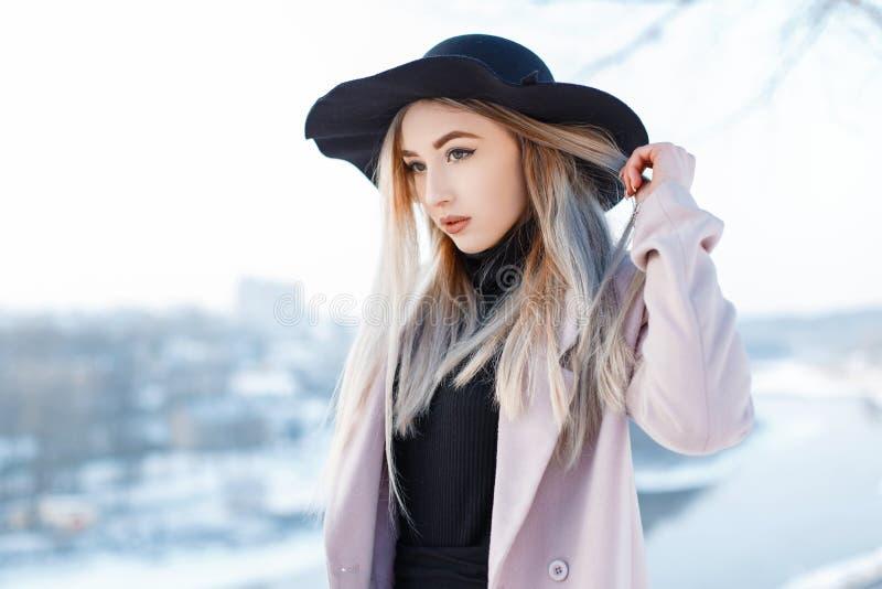 Het charmeren van elegante jonge vrouw in een uitstekende hoed in retro stijl in een roze laag in een gebreide kleding bevindt zi stock afbeeldingen