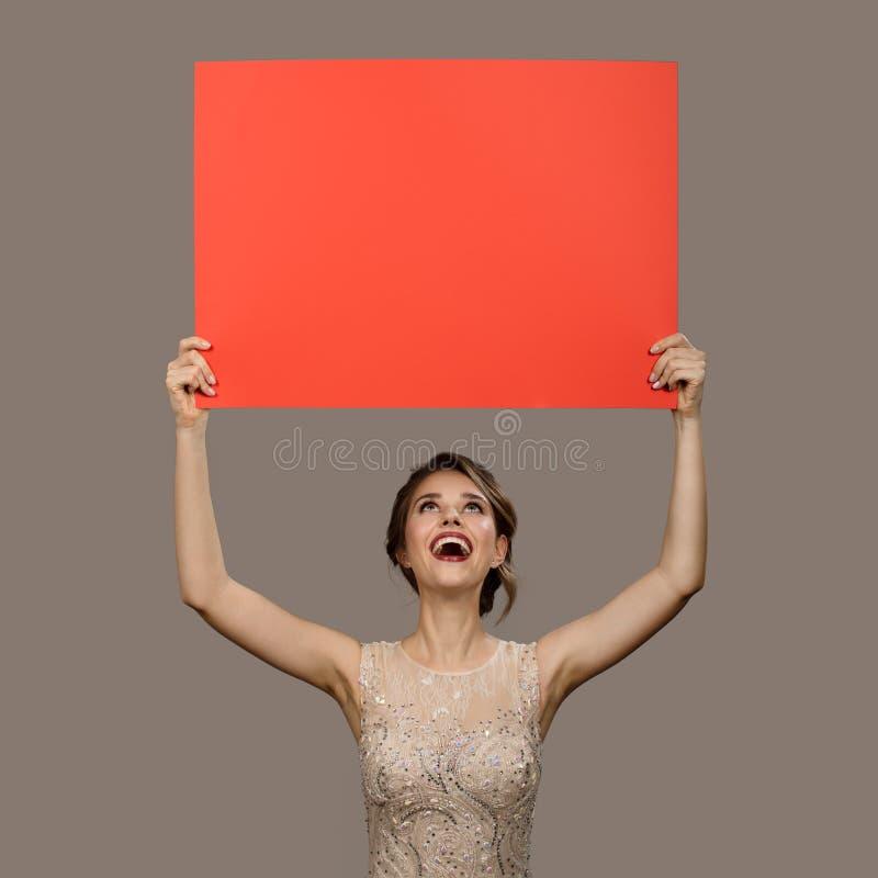 Het charmeren van gelukkige vrouw die grote rode document lege spatie houdt stock afbeelding