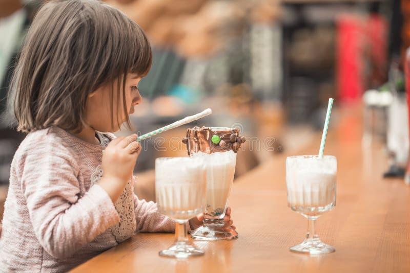 Het charmeren van Grappig meisje drinkt een milkshake royalty-vrije stock fotografie