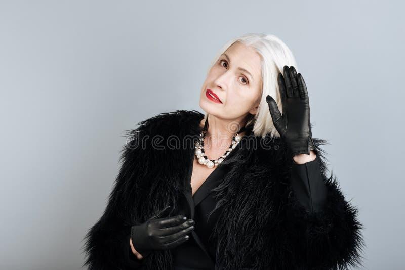 Het charmeren van hogere aantrekkelijke vrouw wat betreft haar haar stock foto's