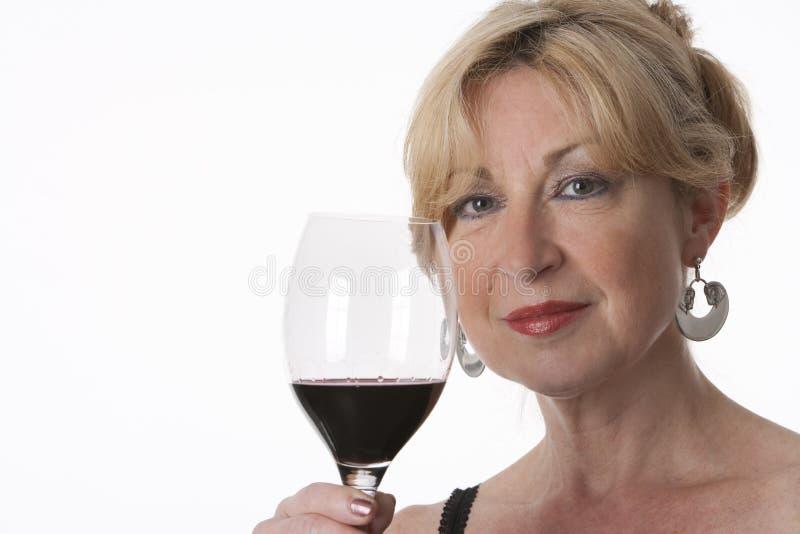 Het charmeren van Hogere Vrouw die een Glas Rode Wijn houdt royalty-vrije stock foto