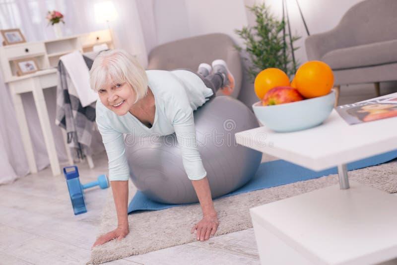 Het charmeren van hogere vrouw die plank doen terwijl het liggen op yogabal stock foto's