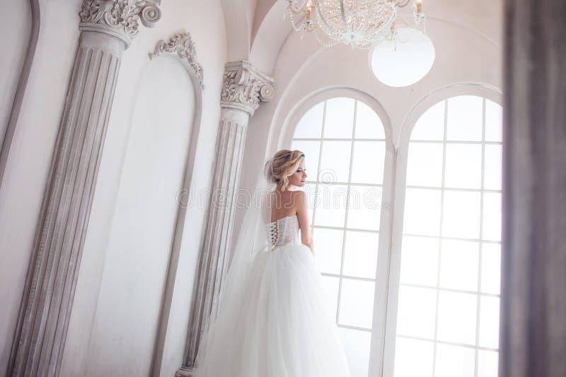 Het charmeren van jonge bruid in luxueuze huwelijkskleding Mooi meisje, de fotostudio royalty-vrije stock fotografie