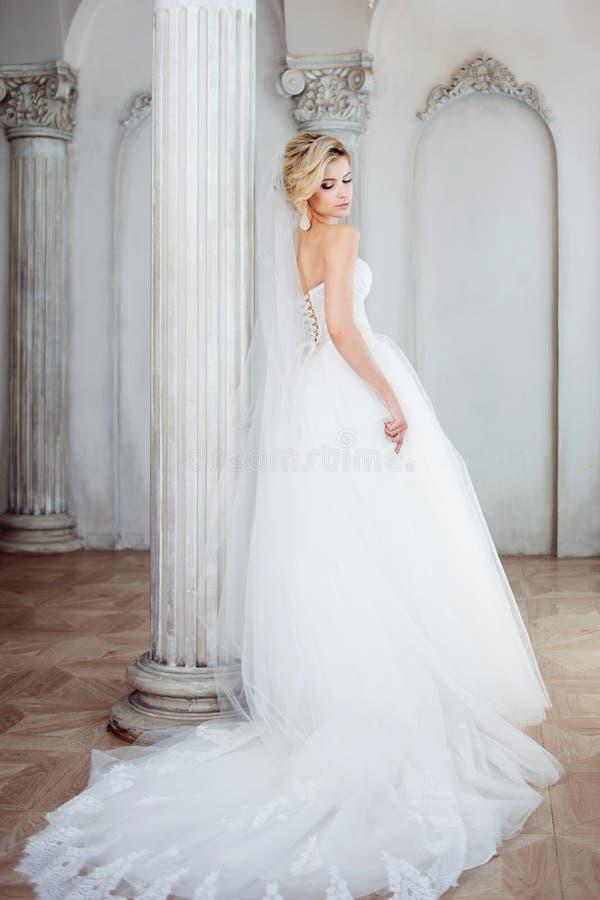 Het charmeren van jonge bruid in luxueuze huwelijkskleding Mooi meisje, de fotostudio stock foto's