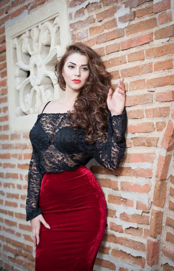 Het charmeren van jonge donkerbruine vrouw in zwarte kantblouse, rode rok en hoge hielen dichtbij de bakstenen muur. Sexy schitter stock foto's