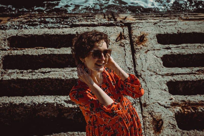 Het charmeren van jonge glimlachende vrouw die in rode kleding met kort krullend haar camera bekijkt De vrouwelijke retro zonnebr stock fotografie