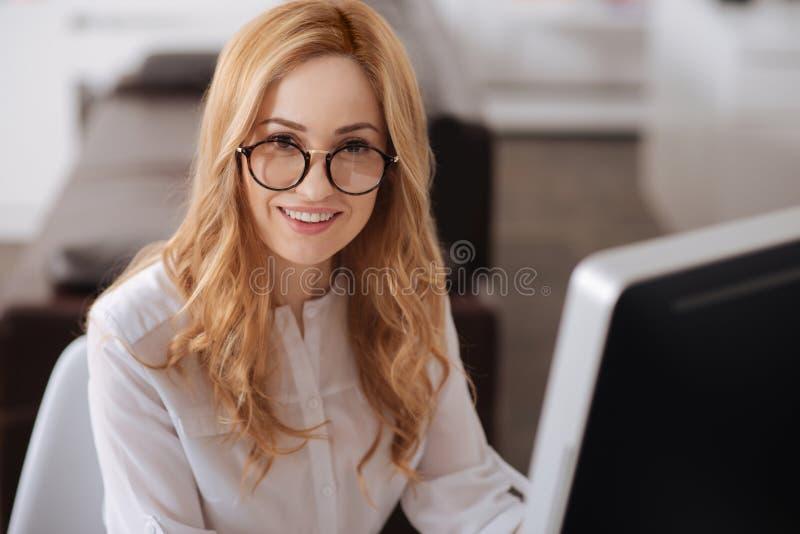 Het charmeren van jonge manager die van verantwoordelijkheden genieten op het werk royalty-vrije stock afbeeldingen
