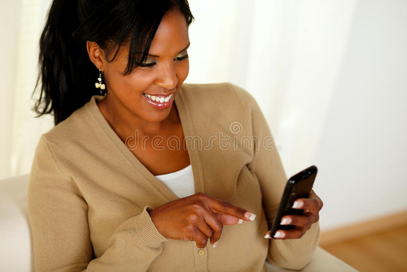 Het charmeren van jonge vrouw die aan cellphone richt stock afbeeldingen