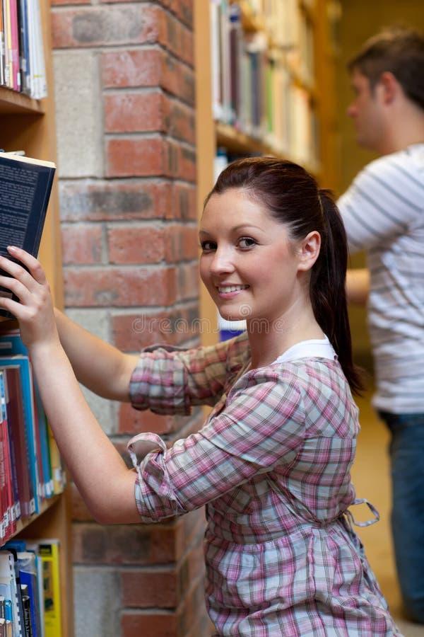 Het charmeren van jonge vrouw die een boek zoekt stock afbeelding