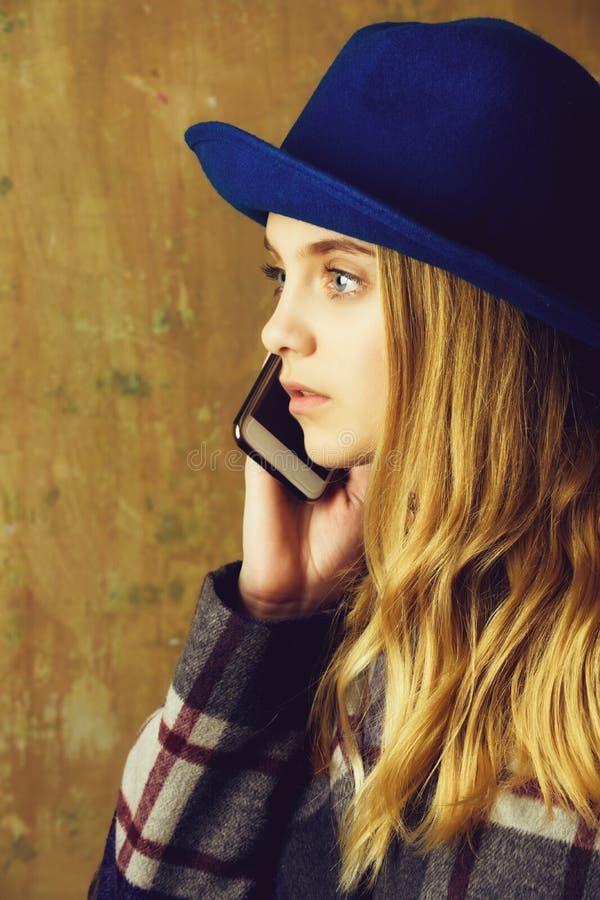 Het charmeren van jonge vrouw die in hoed op mobiele telefoon spreken stock afbeeldingen