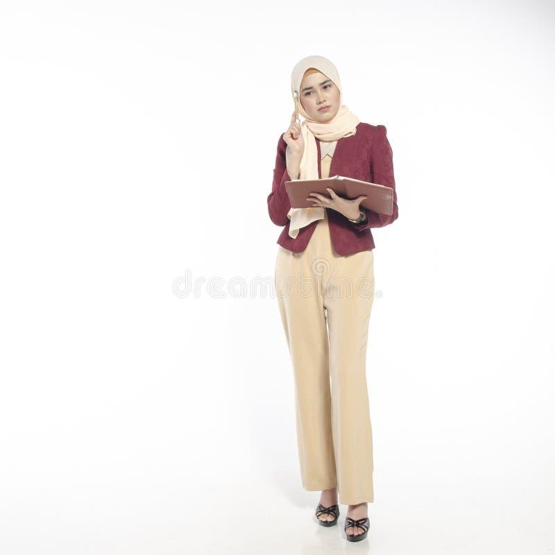 Het charmeren van jonge vrouw die met hijab terwijl het houden van boek op w denken royalty-vrije stock foto's