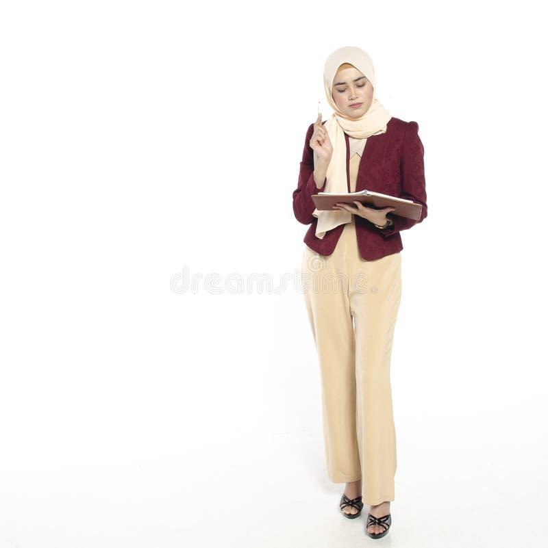 Het charmeren van jonge vrouw die met hijab terwijl het houden van boek op w denken stock afbeelding