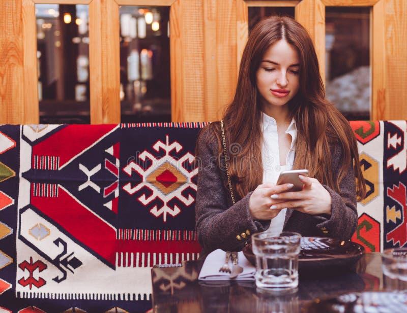 Het charmeren van jonge vrouw die met mooie glimlach goed nieuws op mobiele telefoon lezen tijdens rust in Etnische koffiewinkel, stock afbeelding