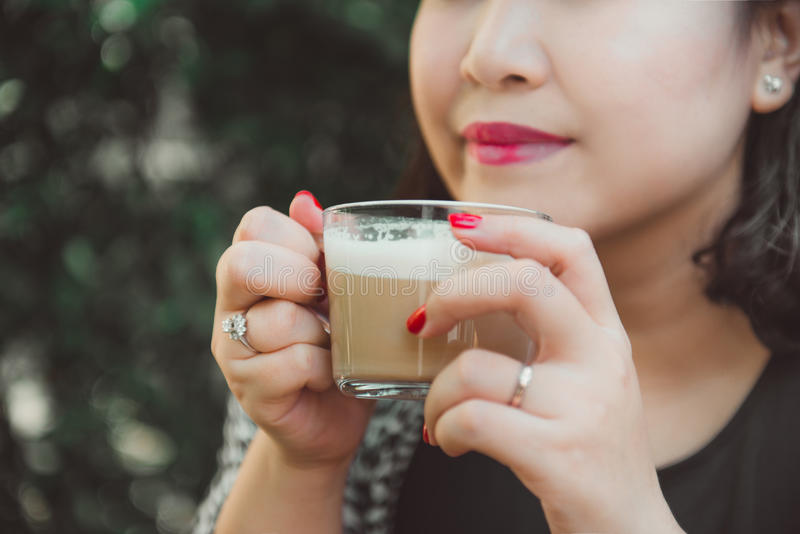 Het charmeren van jonge vrouw die van koffie in koffie genieten royalty-vrije stock afbeeldingen