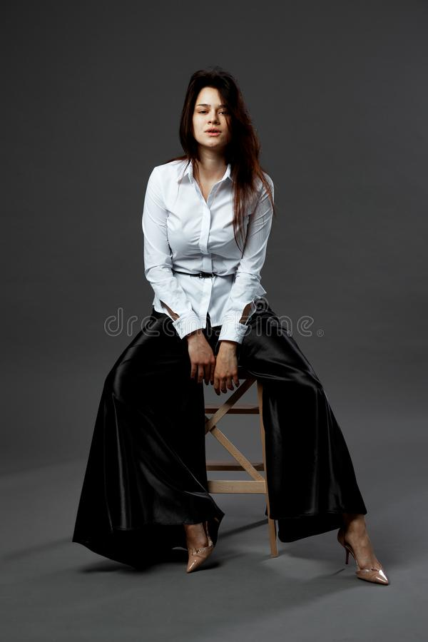Het charmeren van jonge vrouw gekleed in wit overhemd met zwart band en brede zwarte broeken zit op een houten kruk op royalty-vrije stock foto