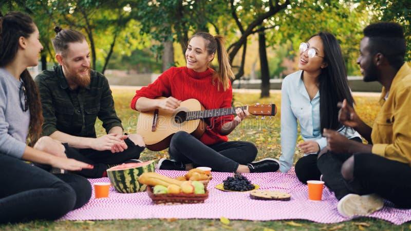 Het charmeren van jonge vrouw speelt de gitaarzitting op deken met vrienden op picknick, slaan de meisjes en de kerels handen royalty-vrije stock foto's