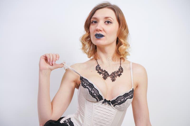Het charmeren van Kaukasisch blonde in lijfje van de kant het beige lingerie en zwarte rok op witte achtergrond in Studio royalty-vrije stock fotografie