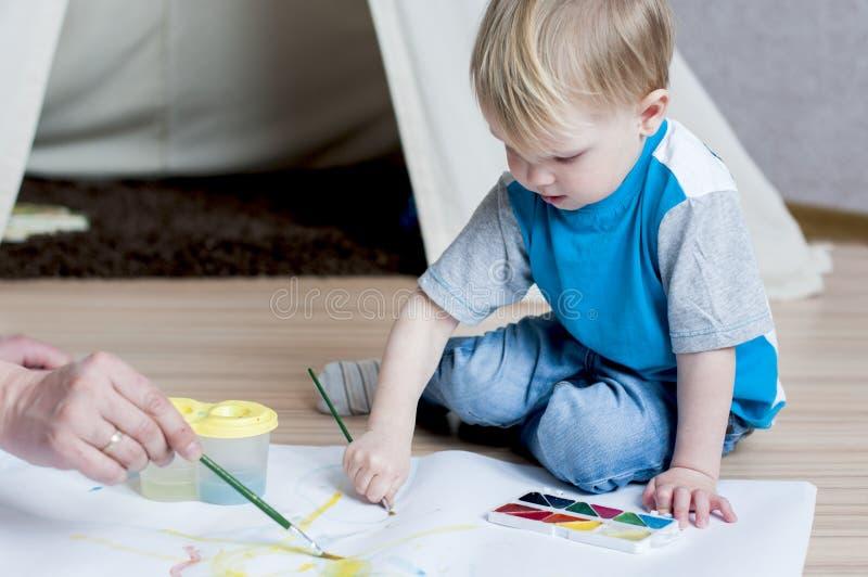 Het charmeren van kleine jongen probeert om met waterverf te schilderen royalty-vrije stock foto's