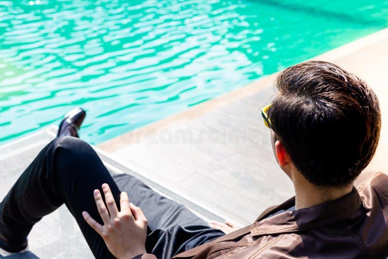 Het charmeren van knappe jonge zakenman zit dichtbij zwembad voor royalty-vrije stock fotografie