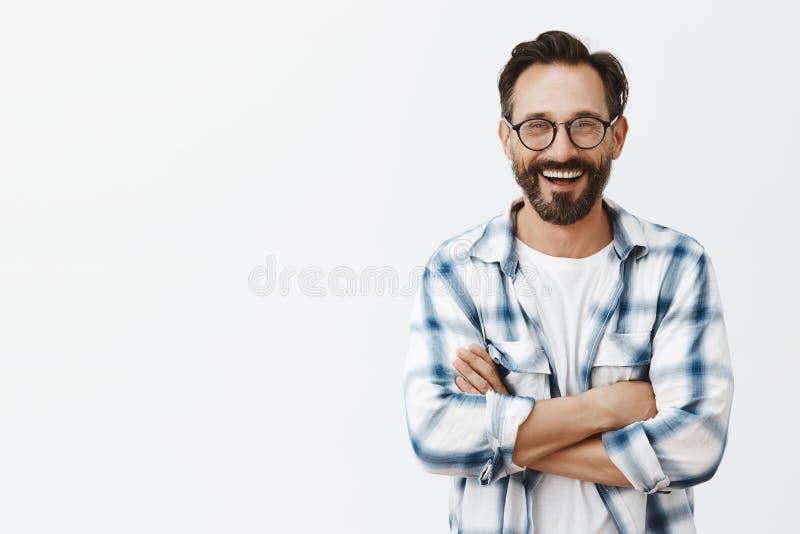Het charmeren van mannelijke professor die van universiteit zich over grijze achtergrond in modieuze zonnebril en gecontroleerd o stock afbeelding