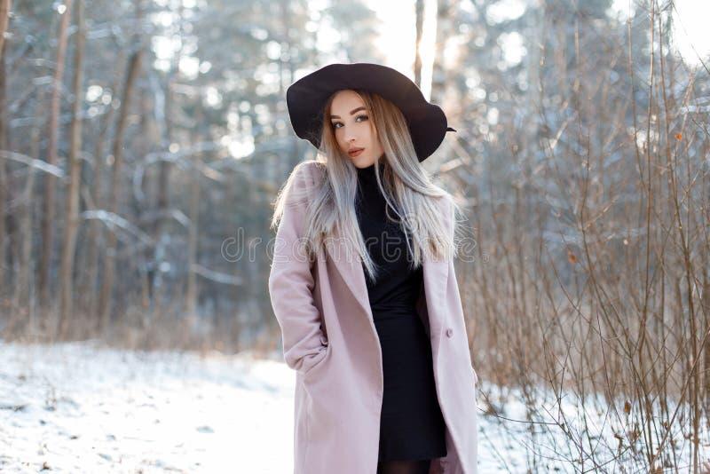 Het charmeren van modieuze jonge vrouw in een luxueuze hoed in een roze laag in een gebreid golf in rok het stellen in het de win stock fotografie