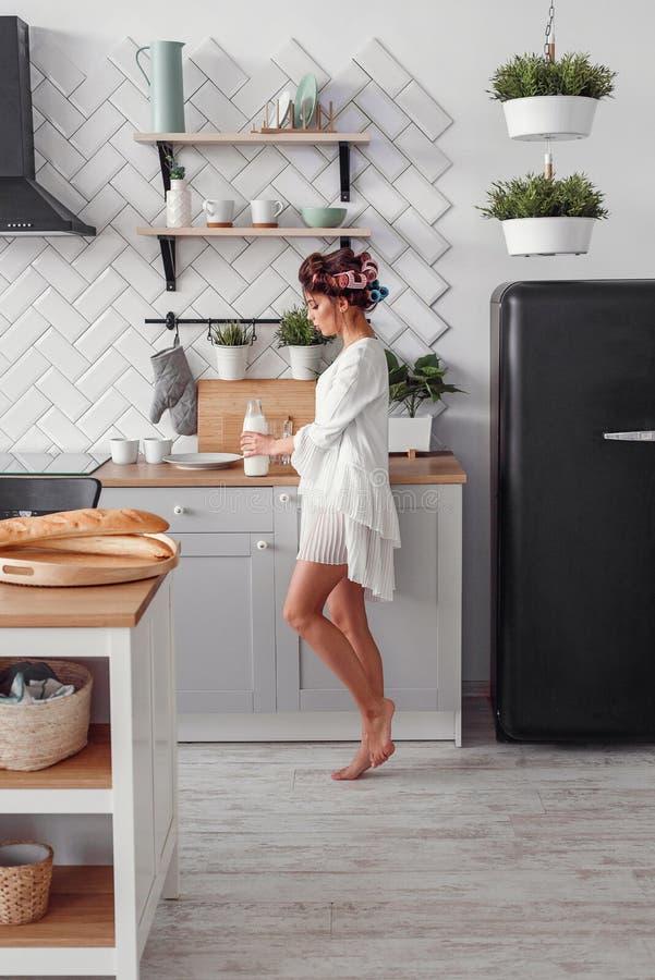 Het charmeren van mooie vrouw die een fles melk houden Het mooie meisje bereidt ontbijt bij moderne comfortabele keuken voor royalty-vrije stock afbeeldingen
