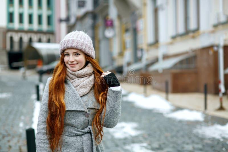 Het charmeren van rood haired meisje die warme de winterkleren dragen die dow lopen royalty-vrije stock foto's